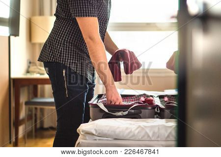 Man Packing Suitcase For Vacation. Person Putting Clothes To Baggagge In Hotel Room Or Home Bedroom.