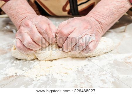 Female Old Hands Knead The Dough On A Table, Close-up