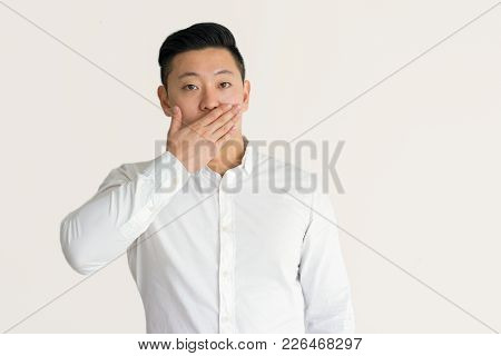 Shocked Young Korean Businessman Knowing Financial News And Covering Mouth With Hand. Amazed Asian M