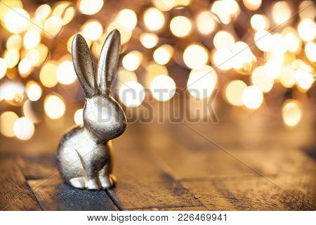 Little Golden Easter Bunny In Front Of Unfocused Lights