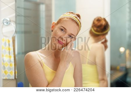 Redhead Girl Applying Beauty Cream In Home Bathroom At Morning. Young Woman Taking Care Of Her Skin,