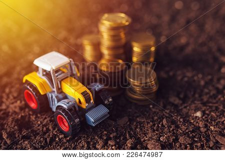 Agricultural Tractor Toy And Golden Coins On Fertile Soil Land, Income From Activity In Agriculture