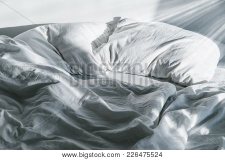 White Crumpled Bed With Pillow And Blnaket Sunlight On Bed
