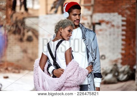 Mixed Race Confident Stylish Male Wears Headphones, Embraces His  Girlfriend, Pose Together Against