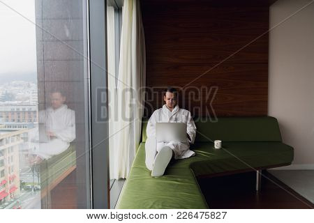 Handsome Young Businessman Wearing Bath Robe On The Bed With Laptop In Modern Room. Self-employed Pe