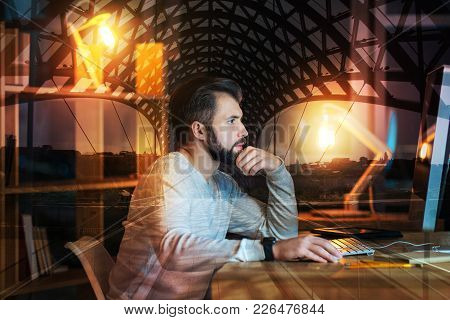 Concentrated Employee. Clever Experienced Freelance Translator Sitting At The Table In Front Of A Mo