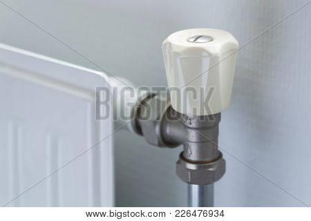 Close Up Of A White Radiator Valve Next To Radiator