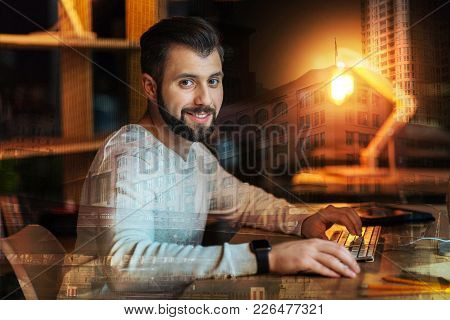 Optimistic Man. Calm Handsome Smiling Man Sitting Comfortably At The Table With His Hands On The Key