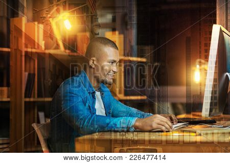 Optimistic Person. Cheerful Handsome Young Man Smiling And Having A Productive Day While Sitting At