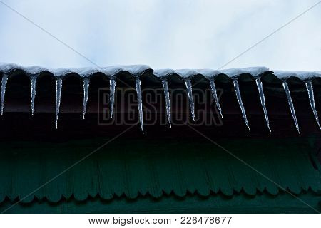 Row Of Icicles On The Roof Of The House Against The Green Wall