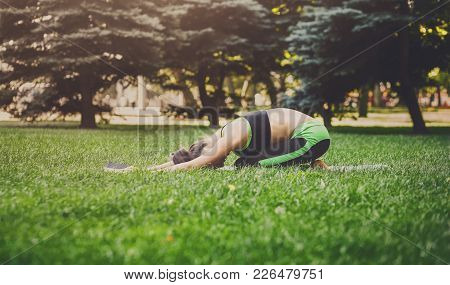 Young Woman Outdoors, Meditation Exercises, Side View. Girl Doing Child Pose For Relaxation. Wellnes