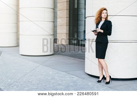 Horizontal Portrait Of Good-looking Businesswoman Dressed In Formal Clothes And Black Shoes With Hig