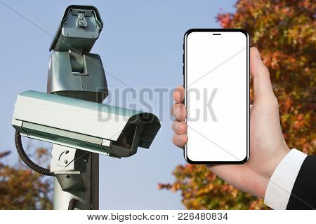 Hand With Phone On Background Of Surveillance Camera. White Screen