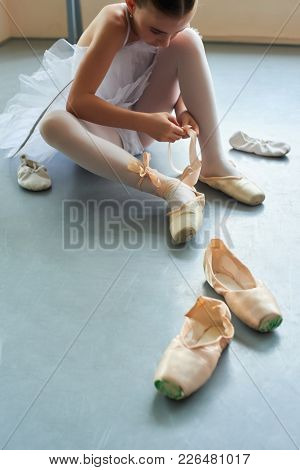 Young Ballerina Tying Pointe Shoes. Cute Ballet Dancer Adjusting Her Ballet Shoes Sitting On Floor.