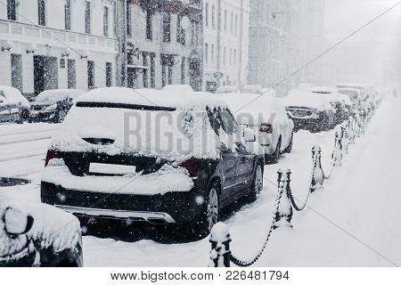 Blizzard, Heavy Snowfall Or Snowstorm Concept. Row Of Cars Covered With Snow During Snowy Winter Wea