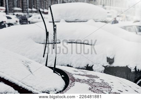 Cars Covered With Thick Snow After Snowfall, Frozen Glass, Winter Weather. City Scape. Windshield Co