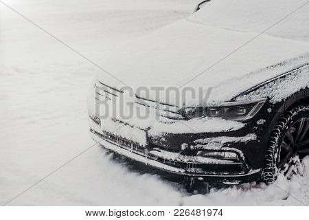 Outdoor Shot Of Car Covered With White Snow, Stuck In Snow During Snowfall In Winter. Vehicle On Win