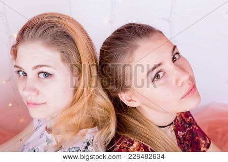 Portrait Of Two Pretty Girls Sitting In A Pose Back To Back
