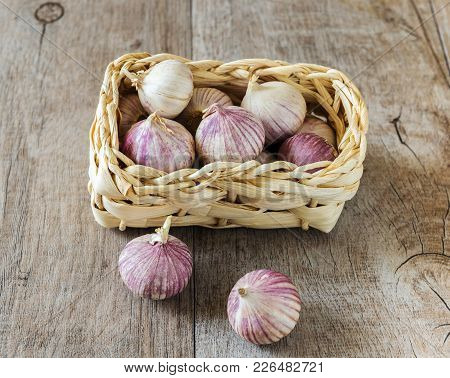 Garlic In The Basket On The Wood Background