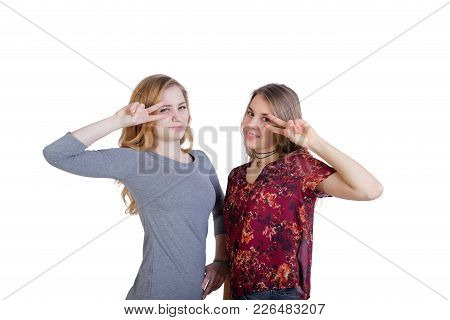 Two Beautiful Long-haired Girls Make A Gesture Of Victory Hands At The Level Of The Face