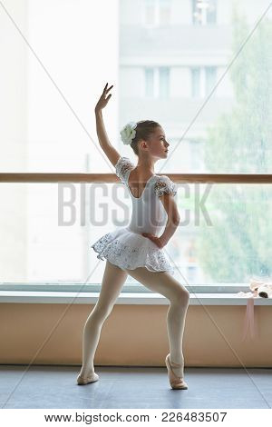 Young Ballerina Standing In Ballet Position. Beautiful Young Ballet Girl In White Dress Posing In Ba