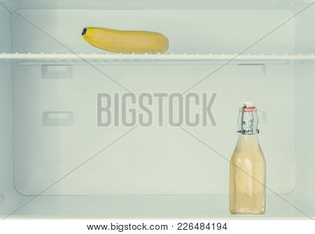 Abstract Photo Of A Yellow Banana And Bottle Inside The Refrigerator