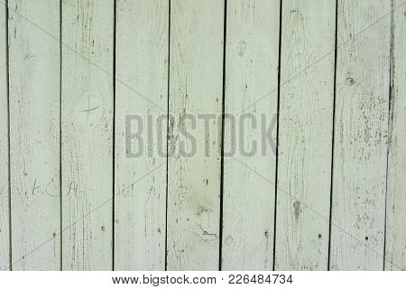 The Old Wooden Fence. Texture Of Naturally Aged Light Green Fence With Cracked Paint. Close Up