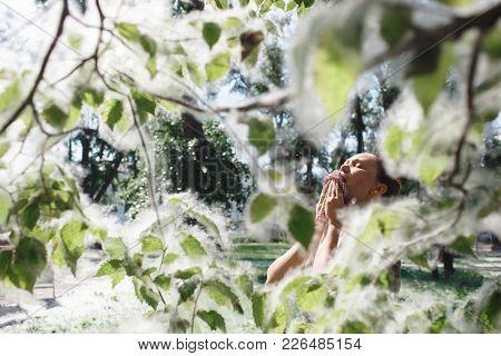 A Young Woman Suffering Spring Pollen Allergy. Poplar Fluff.