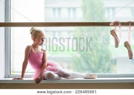 Beautiful Ballet Girl In Pink Leotard. Cute Young Ballerina Sitting On Window-sill And Looking At Po