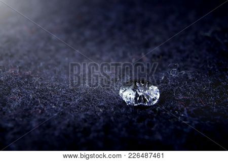 High Detail Close-up Of Sparkling Drop Of Water On Dark Blue Boild Wool - Bright Light Mood With Dee