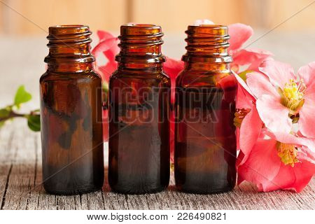 Three Bottles Of Essential Oil With Red Blossoms In The Background