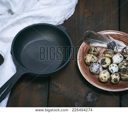Empty Round Cast-iron Frying Pan And Raw Quail Eggs In A Plate On A Brown Wooden Table, Top View