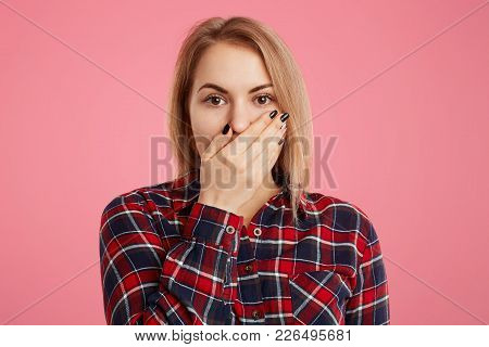 Portrait Of Frightened Beautiful Young Woman Has Manicure, Covers Mouth With Hand, Looks With Puzzle