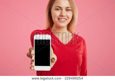 Cropped Shot Of Beautiful Woman Holds Modern Cell Phone In Hands, Blank Copy Space For Your Advertis