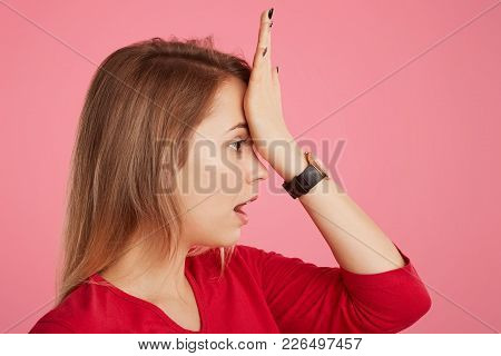 Sideways Portrait Of Beautiful Female Keeps Hand On Forehead, Remembers To Do Something Important, D