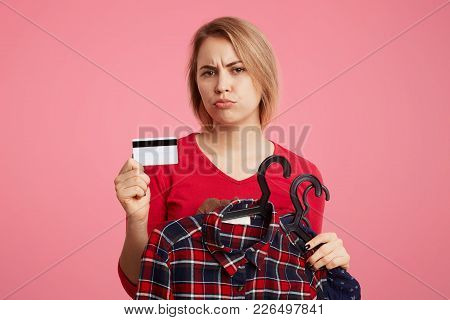 Displeased Female Shopaholic Takes Variety Of Clothes On Hangers, Holds Plastic Card In Hands, Has U
