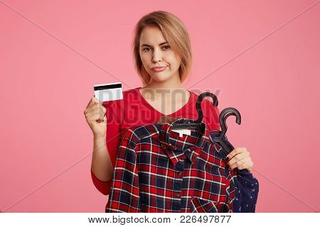 Discontent Young Female Model Poses With Clothes And Plastic Card, Makes Shopping Online, Has No Mon