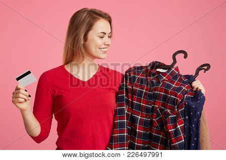 Cheerful Smiling Female Makes Successful Purchases, Looks At Her New Clothes, Holds Plastic Card As
