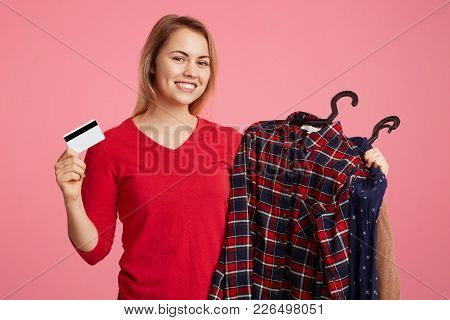 Positive Pleasant Looking Young Female Holds Clothes On Hangers And Plastic Card In Other Hand, Demo