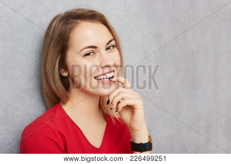 Pretty Female With Happy Expression, Smiles Pleasantly Into Camera, Being Satisfied With Something O
