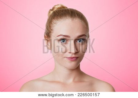 Beautiful Naked Young Woman Wit Hair Knot, Has Healthy Pure Skin, Looks At Camera, Has Blue Eyes, Ap