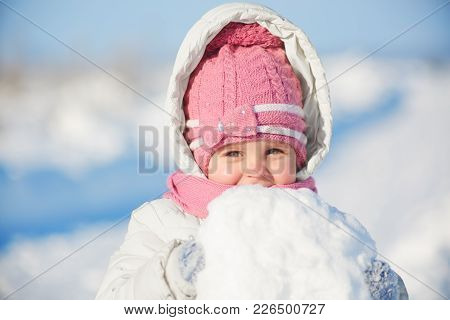 Beautiful Female Kid Wears Warm Pink Hat And Jacket With Hood, Holds Huge Snowball, Poses At Camera