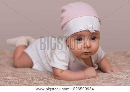Charming Beautiful Lovely Small Female Baby With Plump Cheeks Creeps On Bed, Looks Innocently On Som