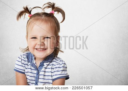 Cheerful Positive Adorable Small Child With Two Pony Tails, Dressed In Striped T Shirt, Expresses Pl
