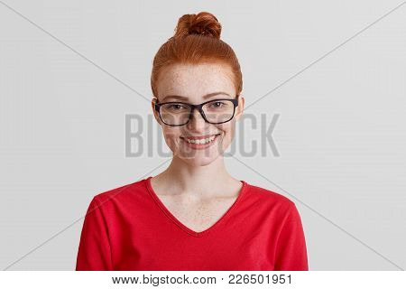 Studio Shot Of Red Haired Young Smiling Female Wears Square Spectacles And Red Sweater, Being In Goo