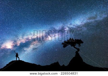 Milky Way, Silhouette Of Woman And Tree Growing From The Rock On The Mountain At Night. Space Backgr