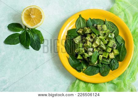 Vitamin Vegetarian Salad With Avocado, Kiwi And Spinach On Yellow Plate. Dressed With Sauce Of Lemon