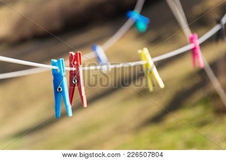 Colorful Plastic Clothes Pegs On White Clothesline, Fashion Business Concept