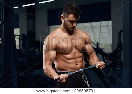 Muscular bodybuilder doing exercises on cable crossover machine in gym.Strong athletic man shows bod