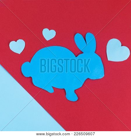 Big Easter Bunny Layed With Paper Hearts Dual Colored Background.